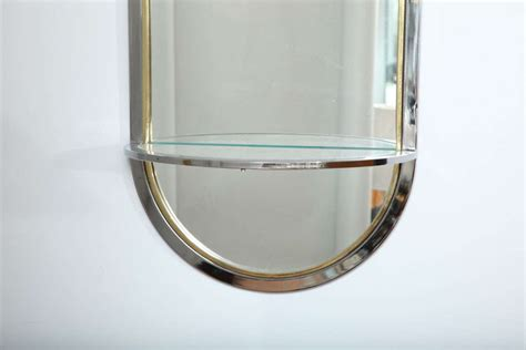 designer elongated oval chrome and brass mirror with glass