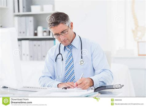 Doctor Table doctor writing on paper at table stock photo image