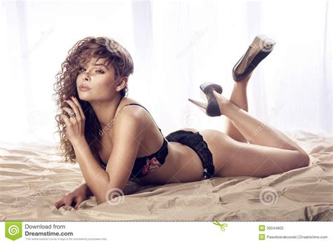 how to look sexier in bed beautiful young woman lying on bed in lingerie stock