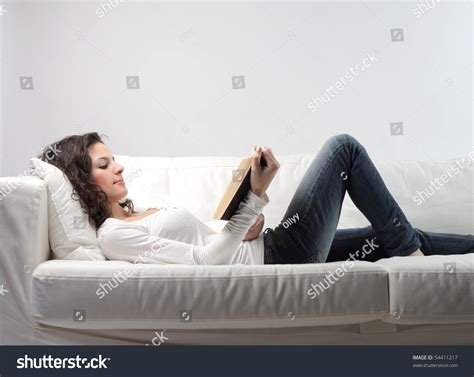 lying on the couch book woman lying on a sofa and reading a book stock photo