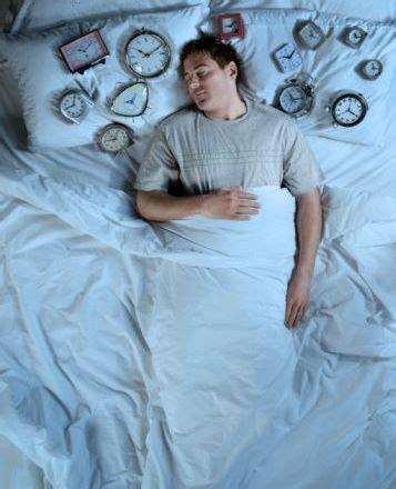 nel letto uomo nel letto circondato da tante sveglie