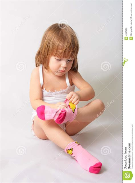young little girls socks small girl is puting on the socks stock photo image 4552480