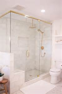Glass and brass shower enclosure is filled with marble tiles lined