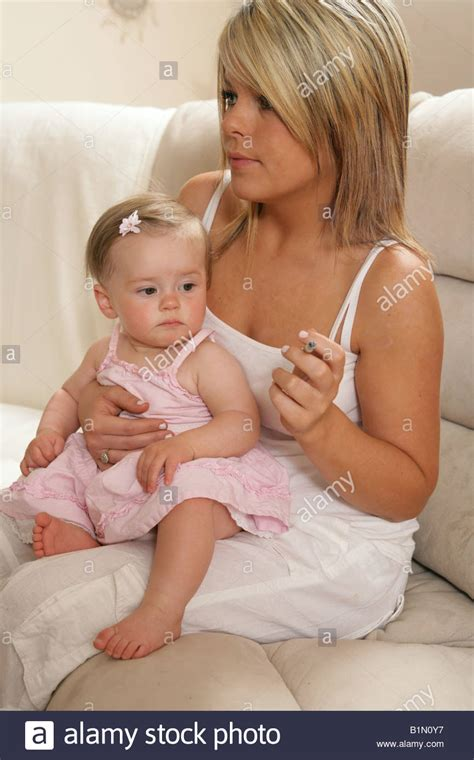 the babys lap book young mother smoking with her nine month old baby sitting on her lap stock photo royalty free