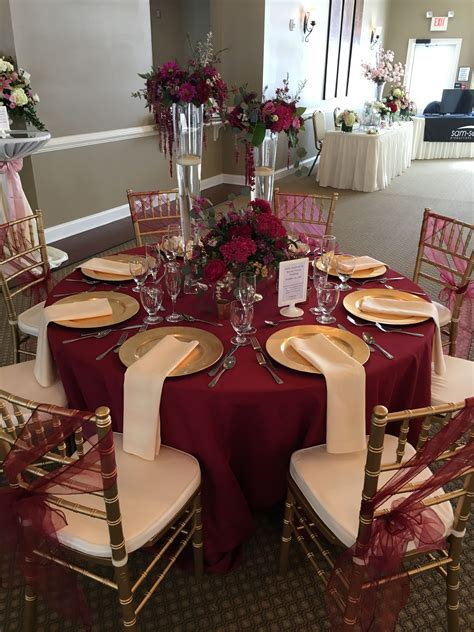 this gorgeous table set up is filled with upgrades floor length burgundy table cloth chagne