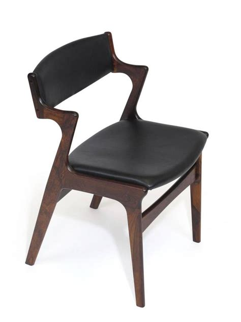 four rosewood and black leather dining chairs for
