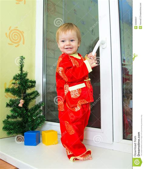 toddler boy new year baby boy in new year costume stands on the window