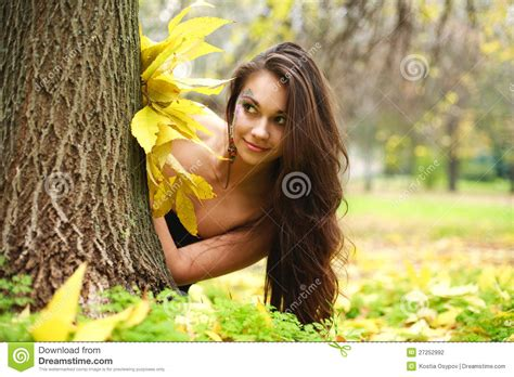 beautiful woman by the tree looking up stock photo image pretty girl hiding behind a tree stock photo image of