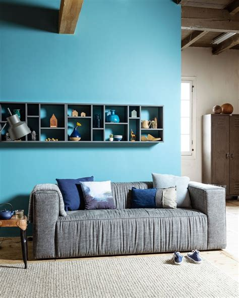 bright blue couch living room with a bright blue wall and grey hard coal