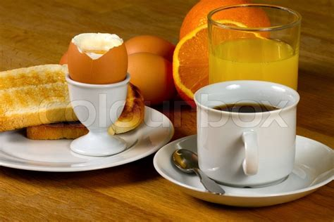 Breakfast: Boiled egg, toast, coffee and fresh orange juice. On Wooden table   Stock Photo