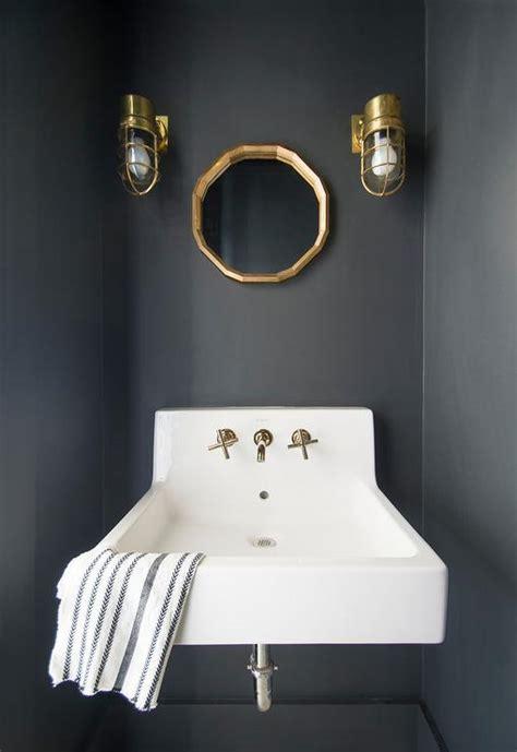 powder room  black walls  gold leaf mirror