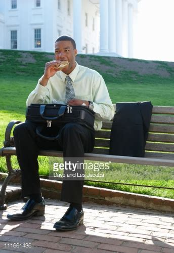 eating bench african american businessman eating sandwich on park bench