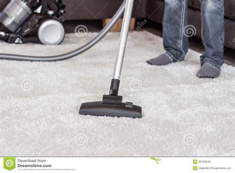 vacuum the carpet a man cleans the carpet with a vacuum cleaner stock photo