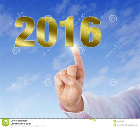 new year touching index finger touching a golden new year 2016 stock photo