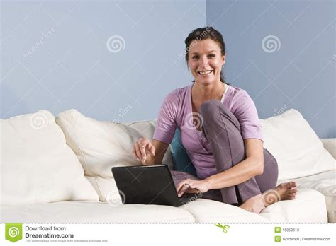 sitting couch woman sitting on couch at home with laptop stock photos