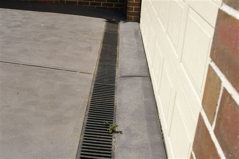 concrete driveway leading to garage and use of specialised drainage solution residential