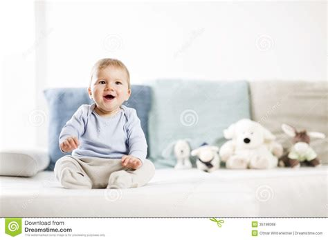 couch baby adorable laughing baby boy sitting on sofa and looking up