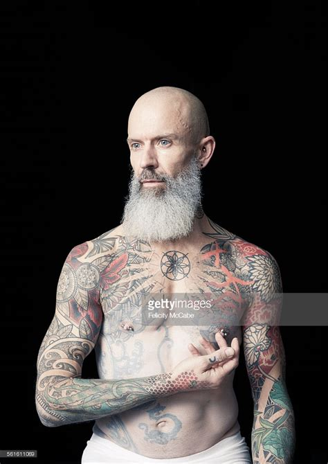 tattoos for hairy men bald tattooed with thick grey beard stock photo