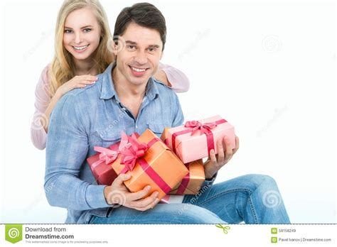 couple gift wallpaper couple holding gifts and looking at the camera stock photo
