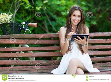 woman sitting on bench woman sitting on bench with digital tablet stock photos