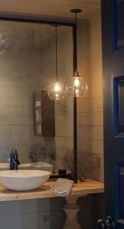powder room lighting a black door opens to a gray powder room features walls