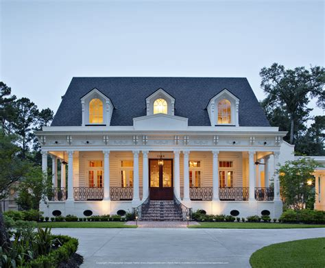 southern architectural styles front door at dusk with cozy porch and white columns on