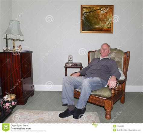 in home sitting sitting in his armchair stock image image of sits 31646125