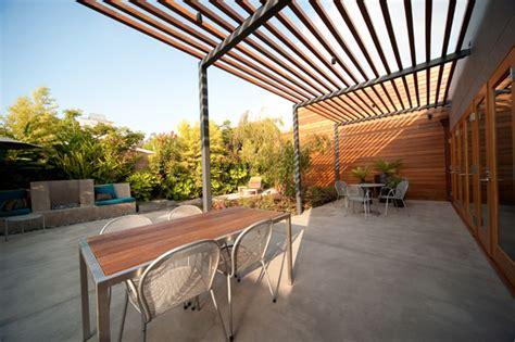Overhead wood and steel trellis create filtered shade.