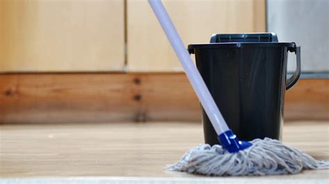 low angle close up footage of someone mopping the kitchen floor with mop and bucket stock video