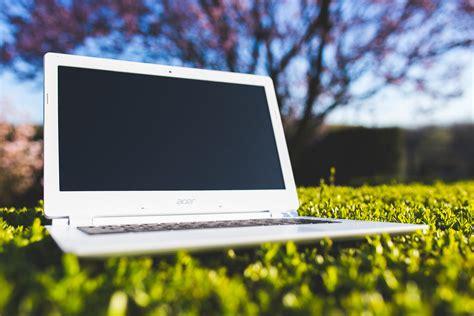 white laptop on a green meadow 183 free stock photo