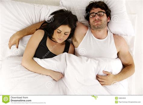 laid in bed man and woman laid in white bed asleep cuddling stock
