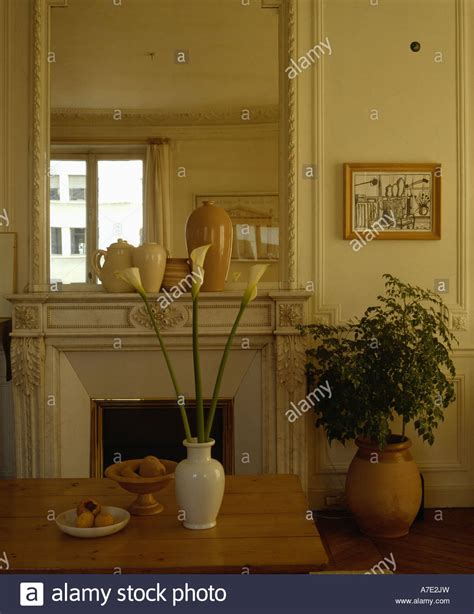 dining table in front of fireplace white lilies in vase on table in front of fireplace below