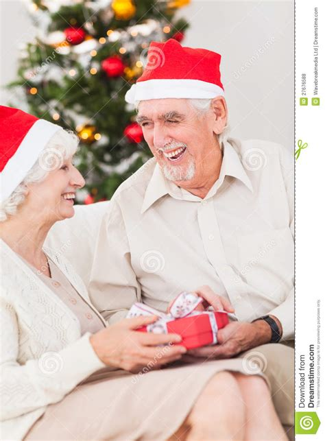elderly couple exchanging christmas gifts royalty free