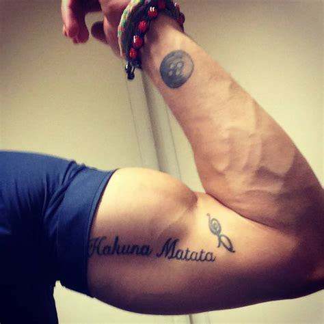 hakuna matata wrist tattoo wrist of a button and bicep saying