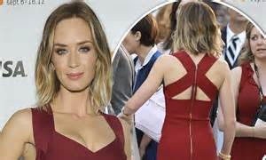 Emily blunt shows off her slim figure in a form fitting maroon dress