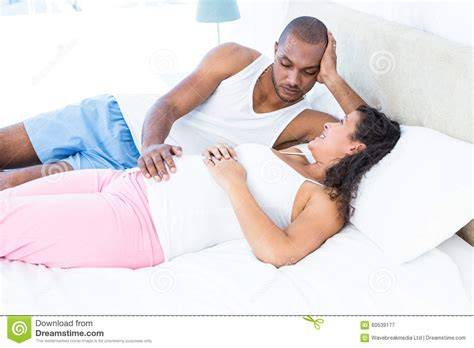 wife in bed happy pregnant wife relaxing with husband on bed stock