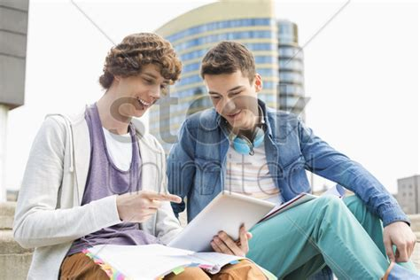 male architect with digital tablet studying plans in happy young male college students using digital tablet