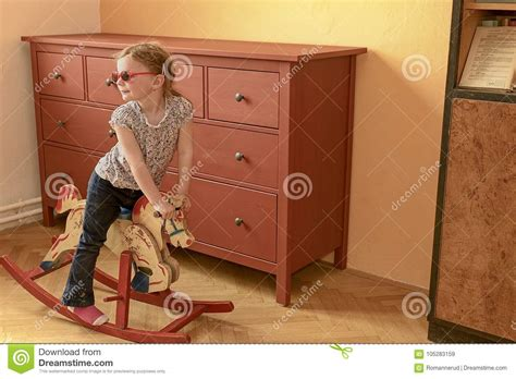 girl  rocking horse small girl wears red glasses