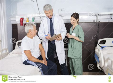 Rehab Doctors by Doctor Explaining Report To Senior Patient In Rehab Center
