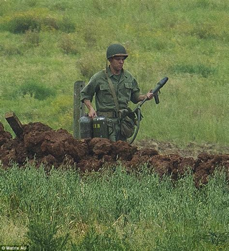 Appeared to be a flame thrower as he made his way across a muddy field