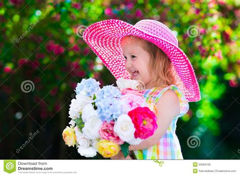 the flower childs play 184643016x little in a hat in blooming summer garden stock photo image 55084132