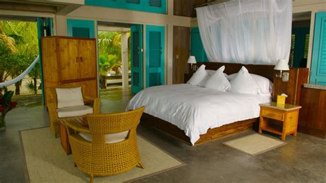 Tropical bedroom design with bold blue door paint feat curtained