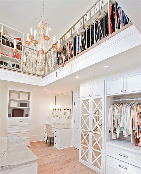 two story walk in closet with a chandelier