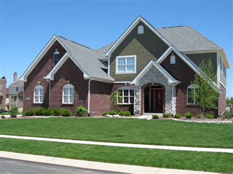 houses with brick and siding luxury home brick shake siding stone archway entrance professional landscaping