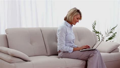 mature couch mature woman on the couch using a laptop in the living