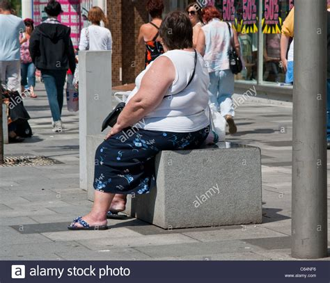 fat lady on bench a square photograph of an obese woman sitting on a bench