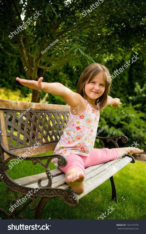 backyard babes child little girl performing gymnastic pose on bench