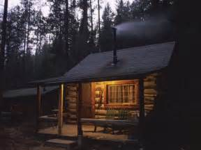 wood smoke rises from the chimney of a log cabin