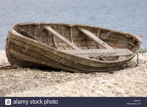 old boat on beach old broken wooden boat on a beach stock photo royalty