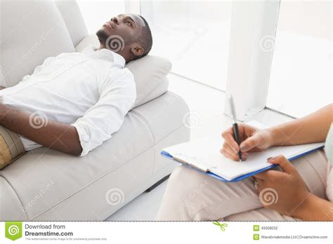 lying on sofa man lying on sofa talking to his therapist stock photo